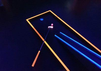 Minigolf-Schläger und -Ball in Schwarzlichtanlage