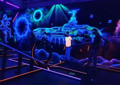 Zwei Spieler in Schwarzlicht-Minigolfanlage